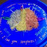 Tuff Tray using spaghetti and tweezers, use of fine motor skills.